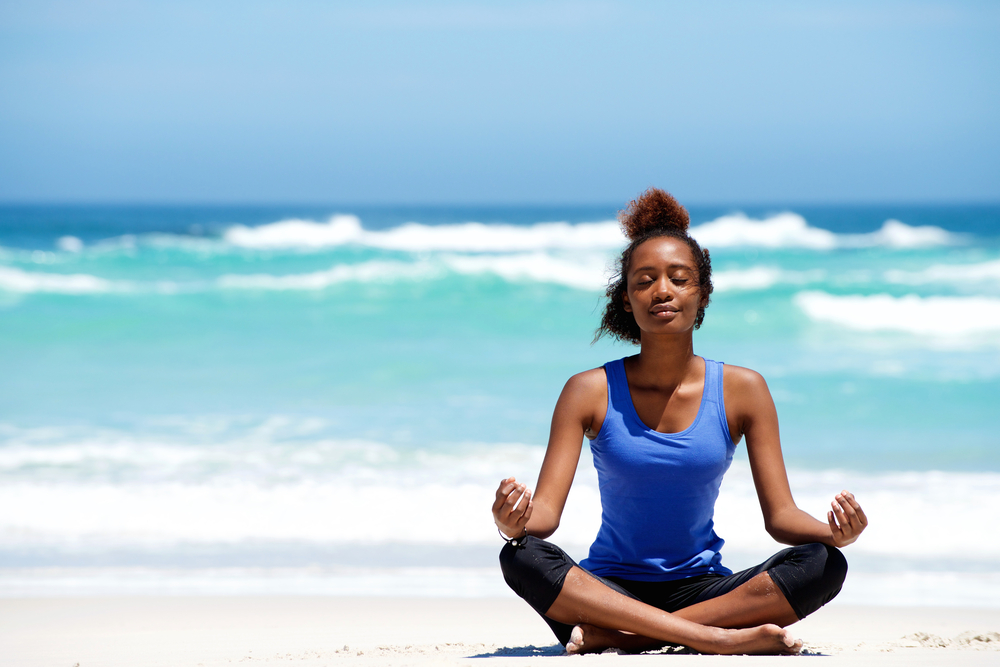 Young black woman doing yoga at the beach.