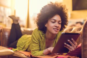 Smiling African American woman enjoying at home and using digital tablet.