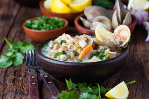 Ceviche raw cold soup salad of seafood shellfish almejas, lemon, cilantro onion in clay bowl on wooden background. Traditional dish of Peru or Chile
