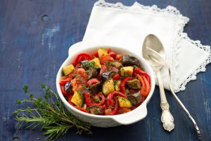 Ratatouille, a traditional French dish of fresh vegetables in a white ceramic bowl on a dark blue background