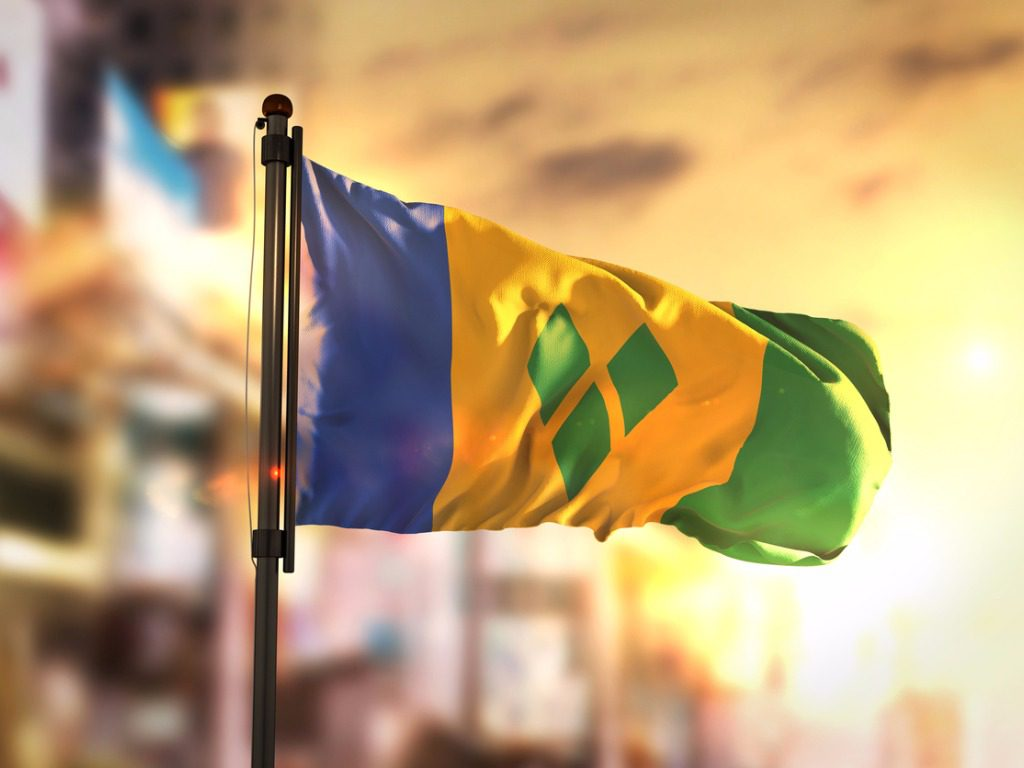 saint-vincent-and-the-grenadines-flag-against-city-blurred-background-picture-id686181404