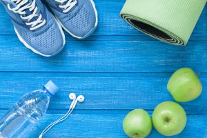 Flat lay sport shoes, bottle of water, mat and earphones
