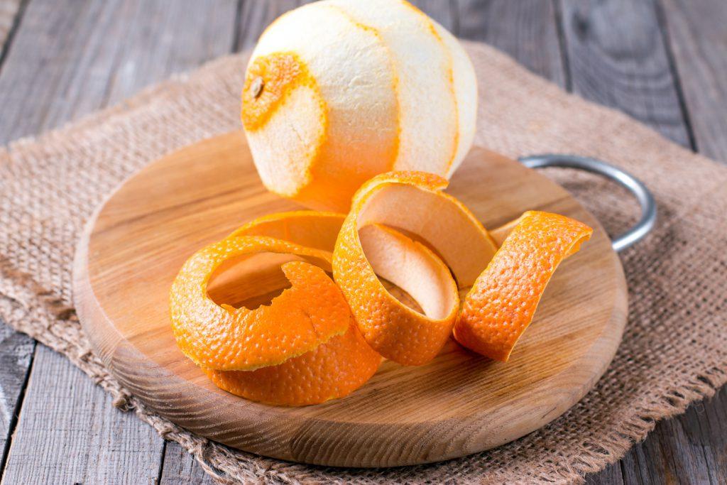 peeled orange on the wooden background