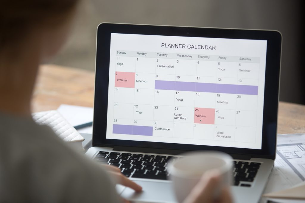 Open laptop on the desk, planner calendar on the screen