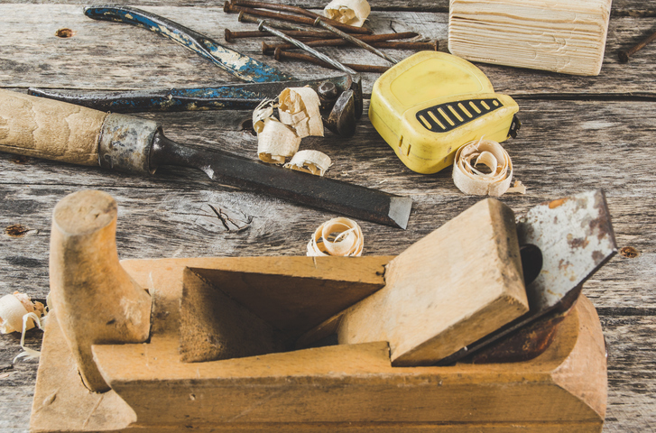 The carpenter tools on wooden bench, plane, chisel,mallet, tape measure, hammer, tongs, pliers, level, nails and a saw