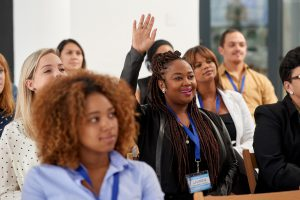 Shot of a young woman raising her hand during a business conference