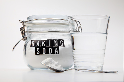 Baking soda in glass jar next to a glass of water
