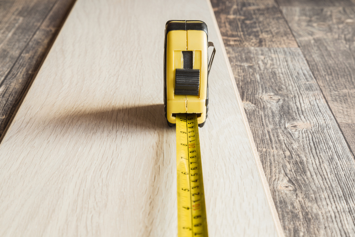 Old, yellow measuring tape on light, new laminate plank. Gray rustic wooden floor change. Carpentry service. Front view.