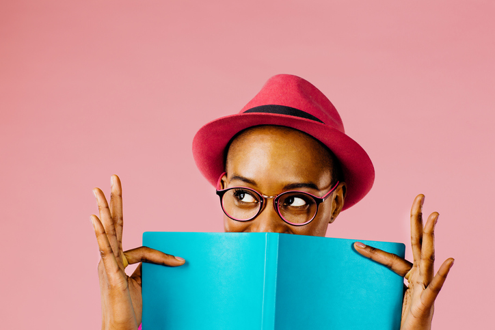 Young woman wearing a pink hat and glasses holding a book.