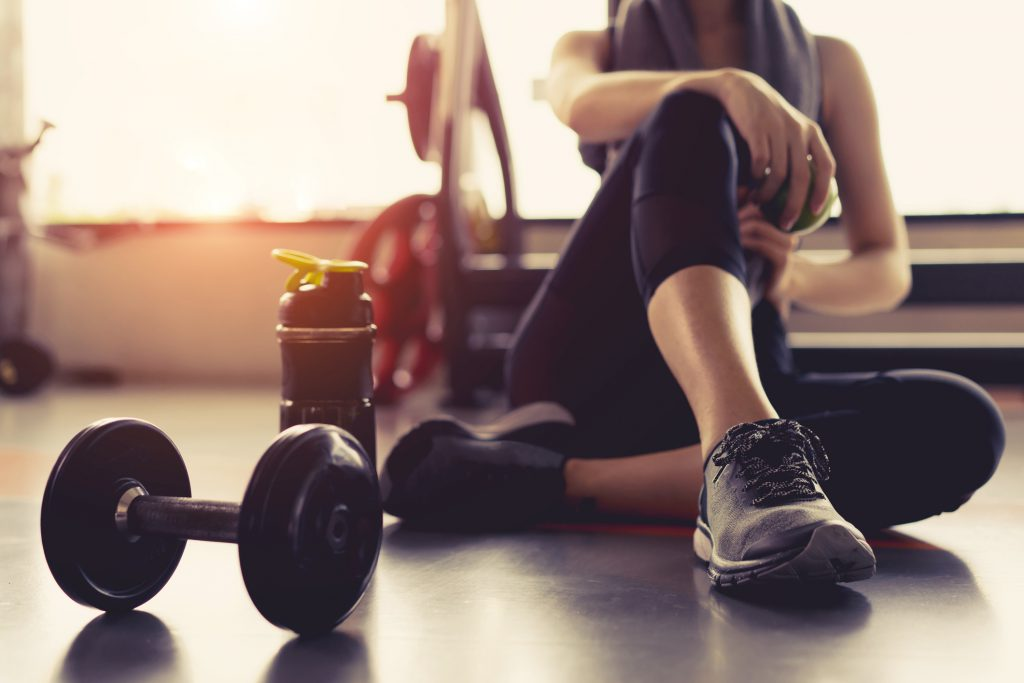 Woman rests in the gym next to a pair of dumbells.