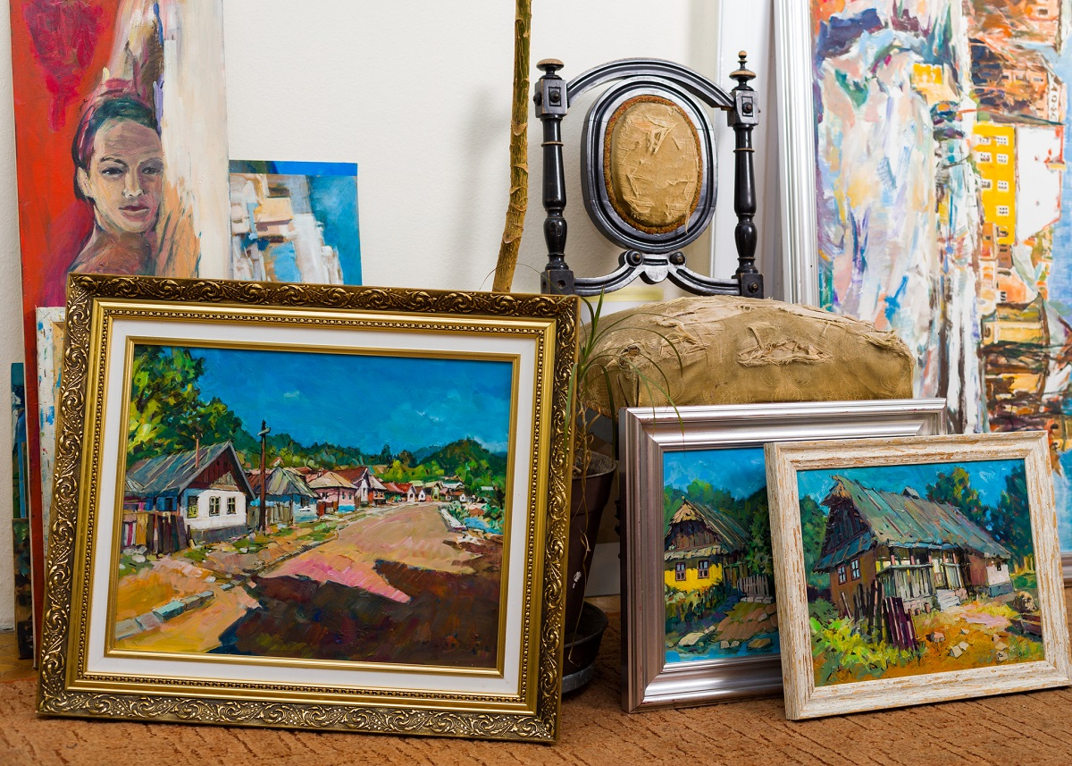 A collection of paintings resting on the floor.
