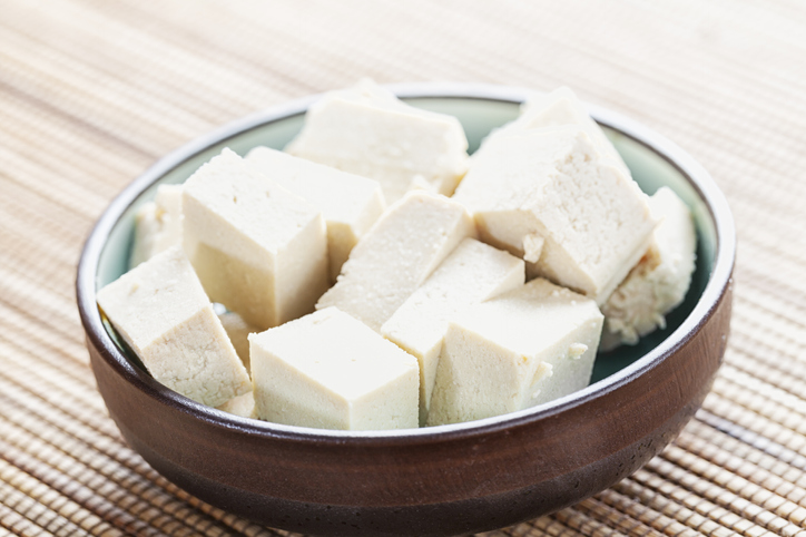 Cubes of tofu in a wooden bowl.