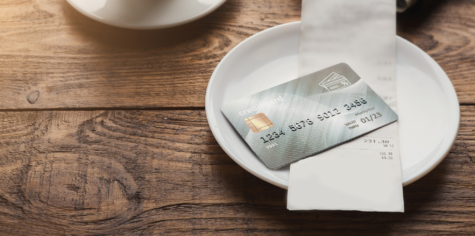 Restaurant bill and credit card in empty white plate on a wooden table.