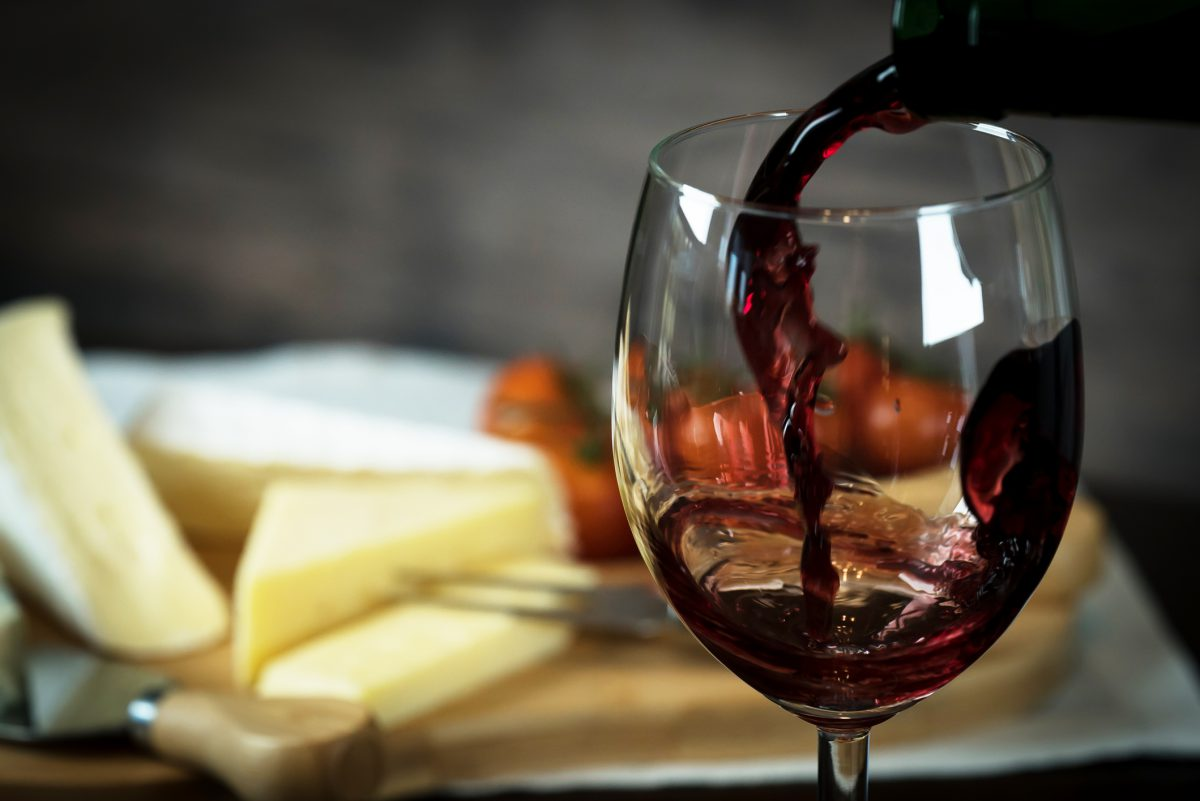 Red wine being poured into a glass with a cheese plate in the background.