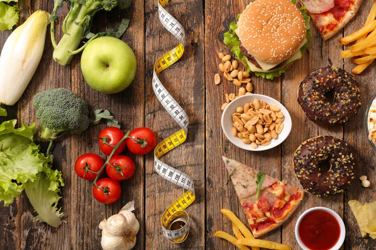 Image showing healthy food on one side of a wooden table and fast food on the other side.