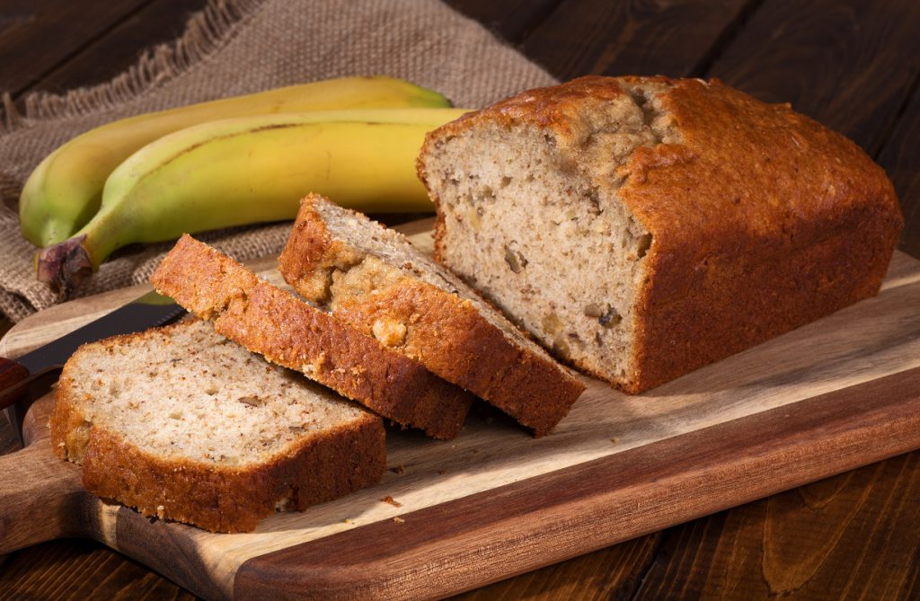 Banana bread on wooden cutting board representing vegan banana bread recipe.
