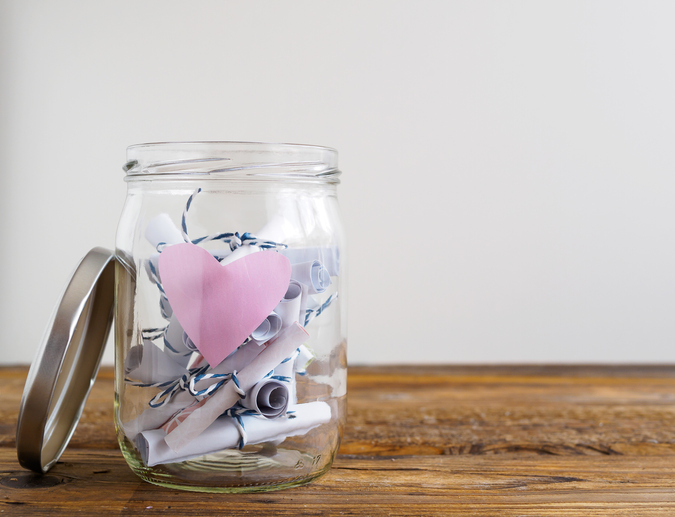 Rolled up notes in a glass jar with a pink heart.