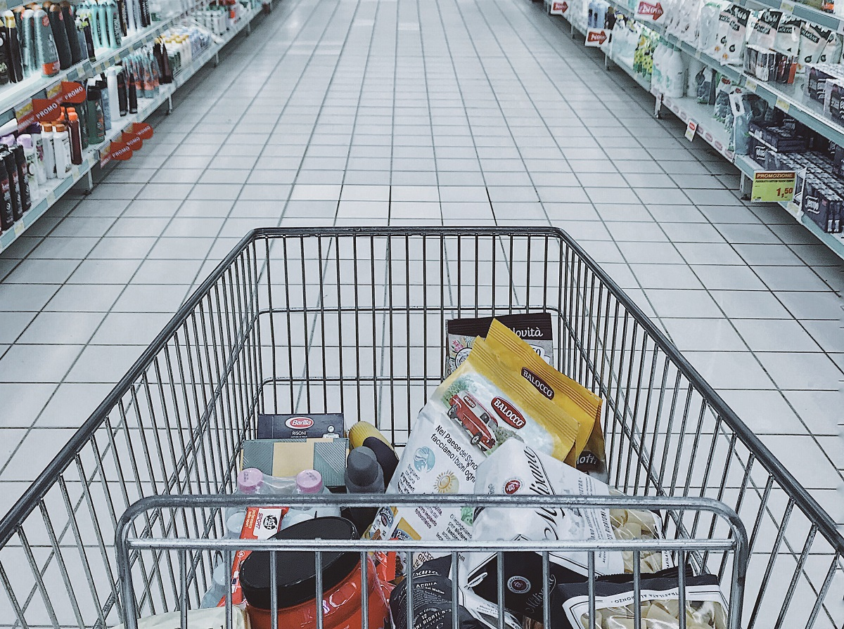 Shopping cart with items in a supermarket aisle.