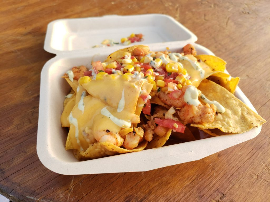 Cheese covered nachoes with seafood in a white Styrofoam box resting on a wooden table.