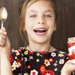 """Young girl eating a treat"""