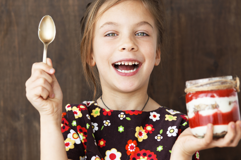 """""""Young girl eating a treat"""""""