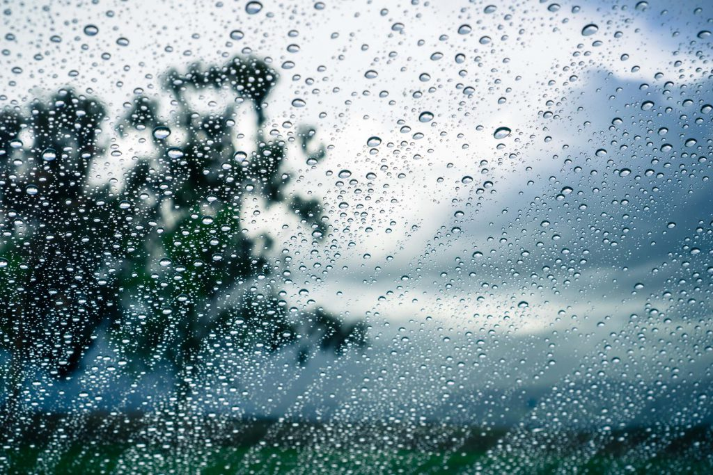 Drops of rain on the window; blurred trees and storm clouds in the background;