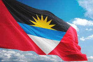 Antigua and Barbuda flag waving isolated cloudy sky background