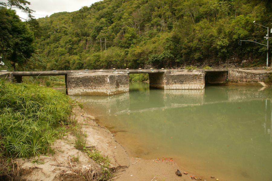A flat, concrete bridge across the Rio Cobre River in Jamaica.