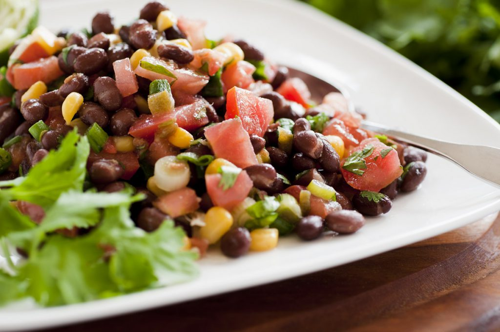 White plate with black beans, corn, and tomatoes.