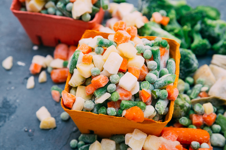 Frozen peas and carrots in an orange container