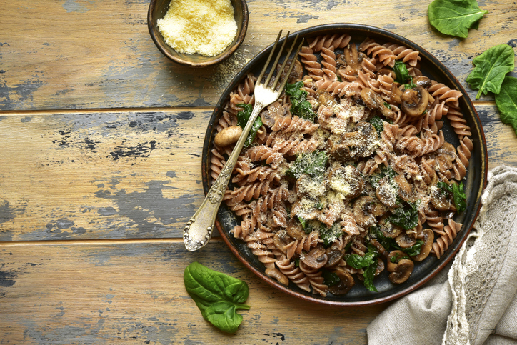 Whole wheat pasta with mushroom and spinach on a plate resting on a wooden table.